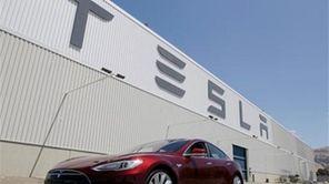 A Tesla Model S drives outside the Tesla