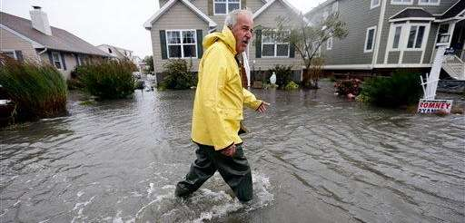 Richard Thomas walks through the flood waters in