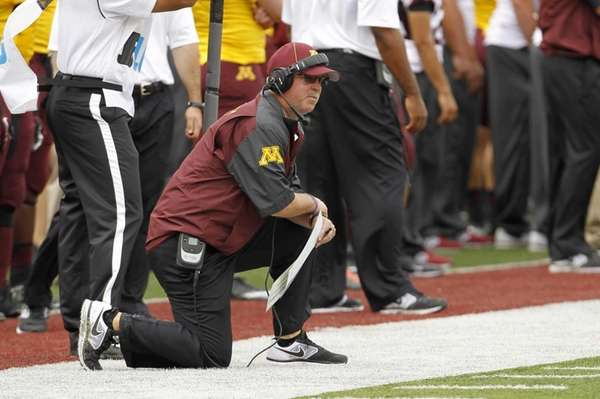 Minnesota head coach Jerry Kill kneels on the