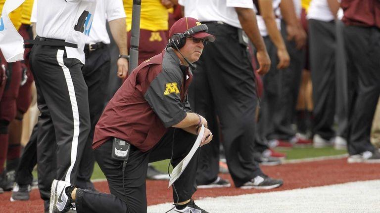 Minnesota head coach Jerry Kill kneels on the
