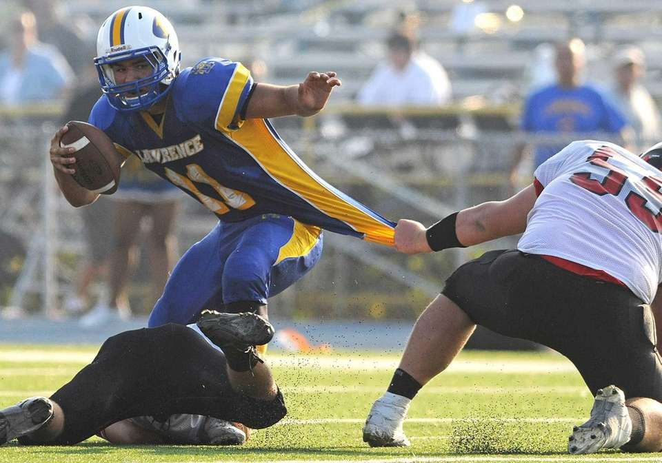 Lawrence quarterback Joe Capobianco gets wrapped up by