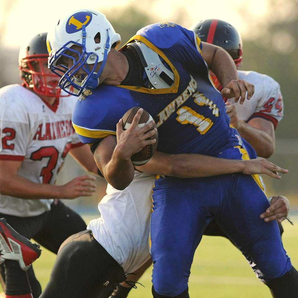 Lawrence quarterback Joe Capobianco gets brought down by