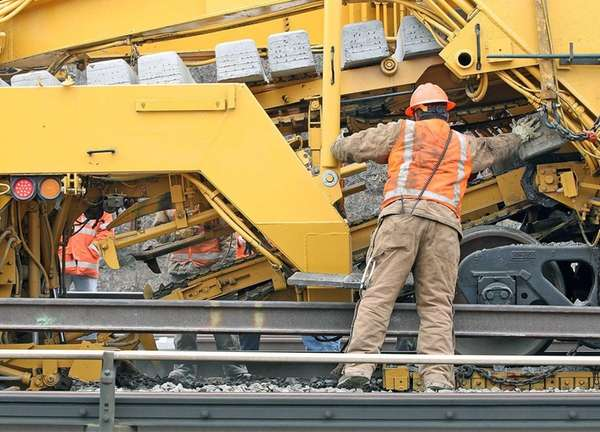 LIRR track maintenance personnel using heavy machinery to