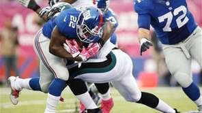 David Wilson (22) breaks a tackle by the