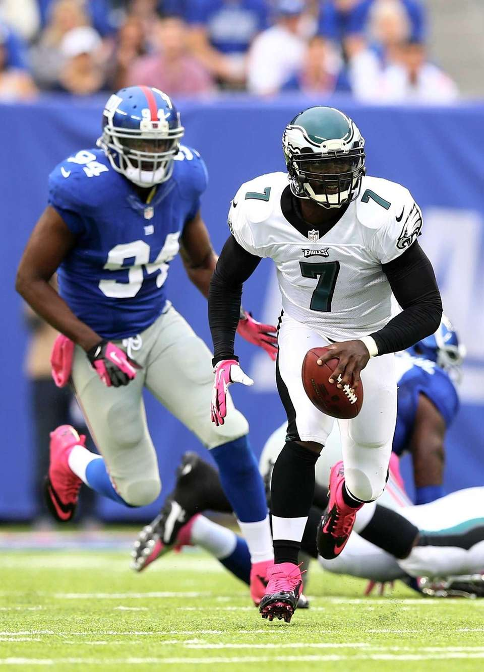 Philadelphia Eagles quarterback Michael Vick scrambles as Mathias