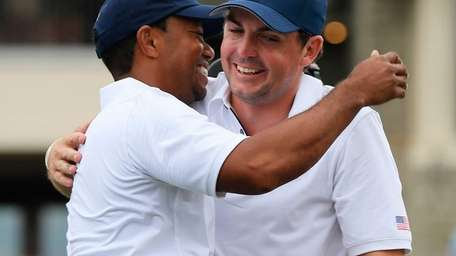 Tiger Woods is hugged by Keegan Bradley on