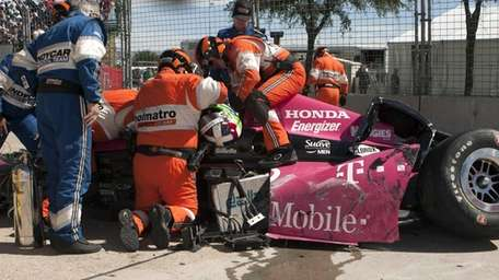 Safety team members work to remove Dario Franchitti