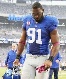 Justin Tuck walks off the field after a
