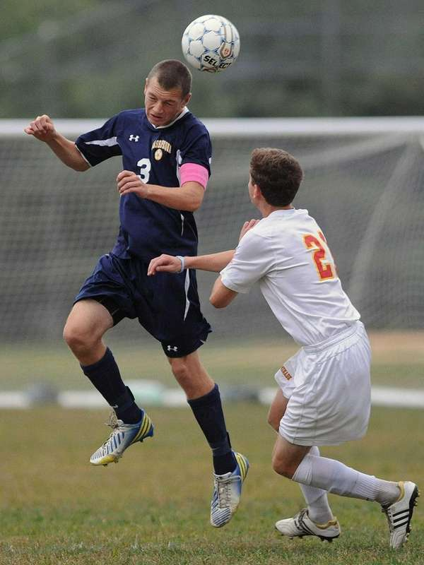 Massapequa's Brandon Merklin, left, heads a ball away