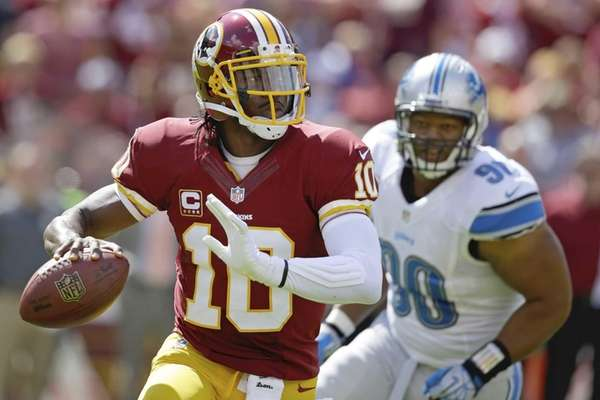 Washington Redskins quarterback Robert Griffin III scrambles away