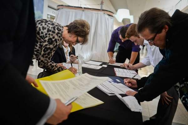 Job seekers fill out applications at the Coach