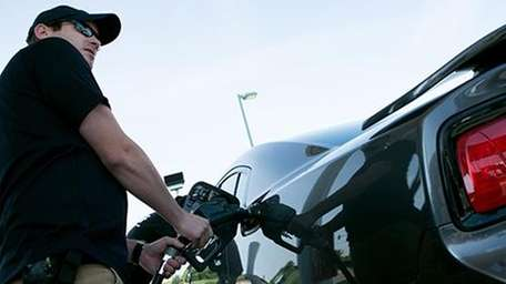 A man fills up his car with gas.