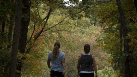 Two women walk around the 2-plus-mile exercise path