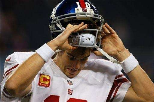 Eli Manning pulls off his helmet during warmups