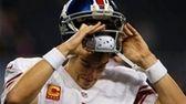 Eli Manning pulls off his helmet during warmups
