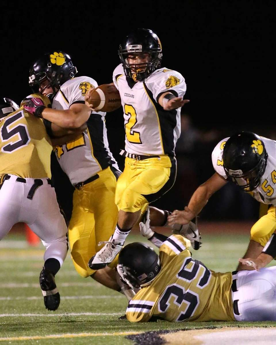 Commack running back Willy Monroy jumps over Sachem