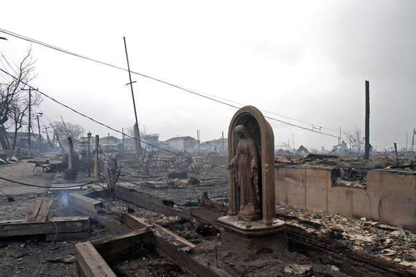 A statue of Blessed Mother overlooks charred remains