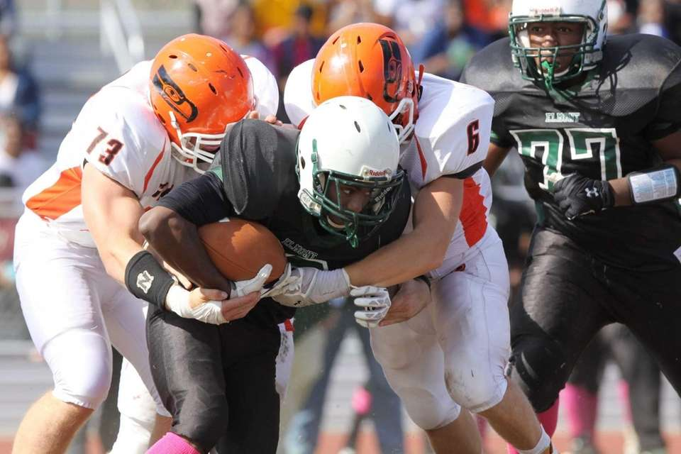 Elmont's Matthew Brutus (center) is tackled by Carey's