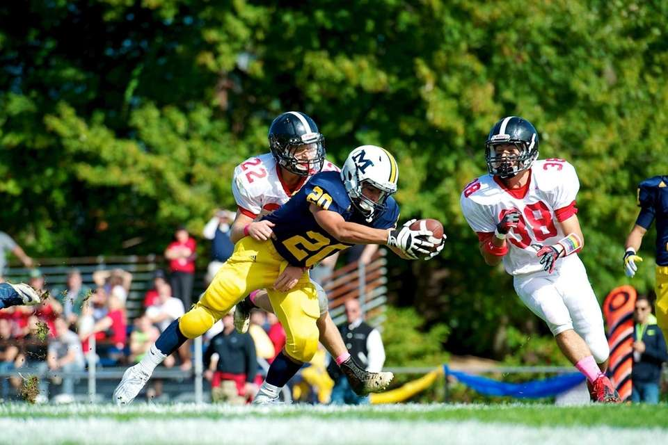 Massapequa running back Nick Capuana (no. 20) dives