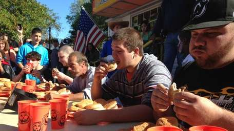 Participants scarf down burgers during a contest at