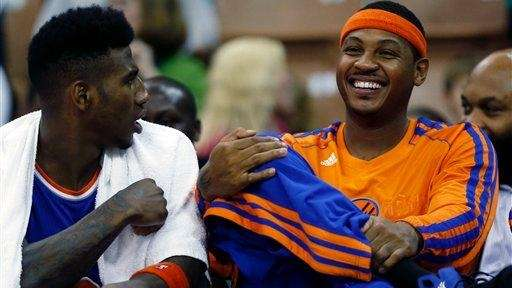 Carmelo Anthony, right, sits on the bench beside