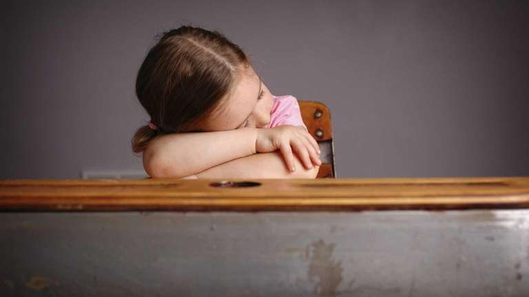 A child sleeping at their desk.
