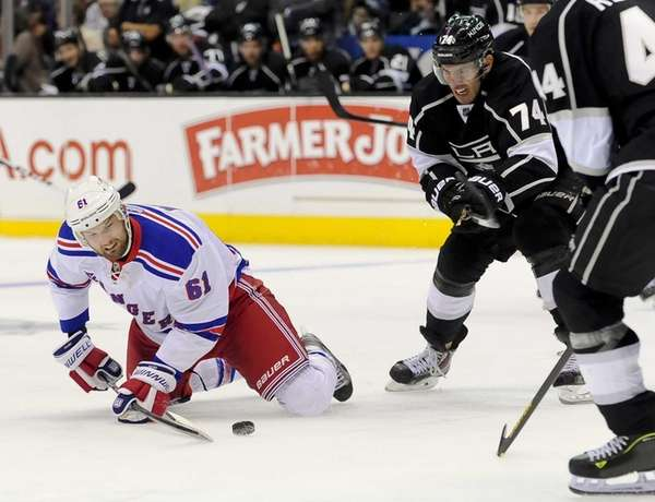 Rick Nash (61) reaches for the puck in