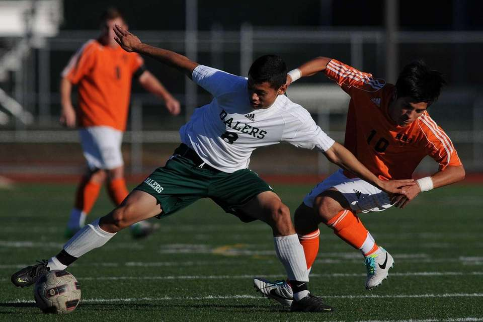 Farmingdale's Carlos Alvarez, left, looks to maintain possession
