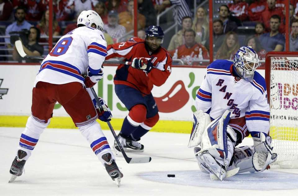 Rangers defenseman Marc Staal, left moves to clear