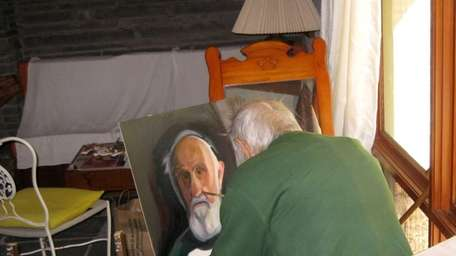 Louis Legakis at home painting the unfinished self-portrait