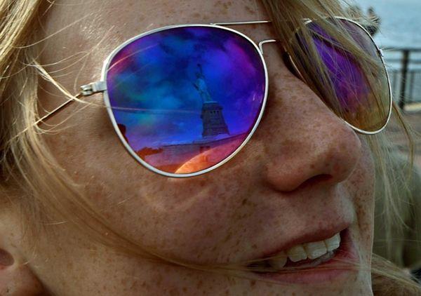 A tourist's sunglasses reflect Lady Liberty as the