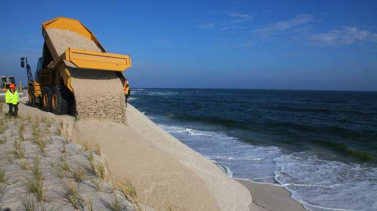 Workers continue to repair damaged dune along Ocean