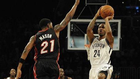 Nets' Chris Johnson attempts a shot past Miami