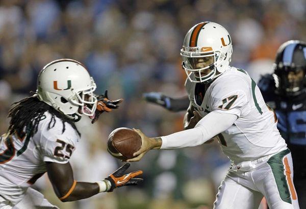 Miami quarterback Stephen Morris hands off to Dallas