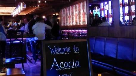A sign in the window of Acacia in