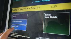 A commuter uses a ticket machine at a