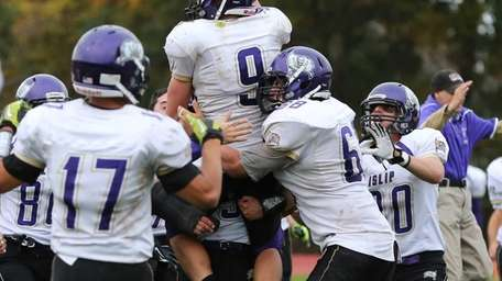 Islip's Ronnie King (no. 9) is hoisted in