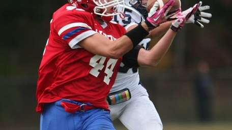 Bellport's Connor Cipp grabs a pass while being