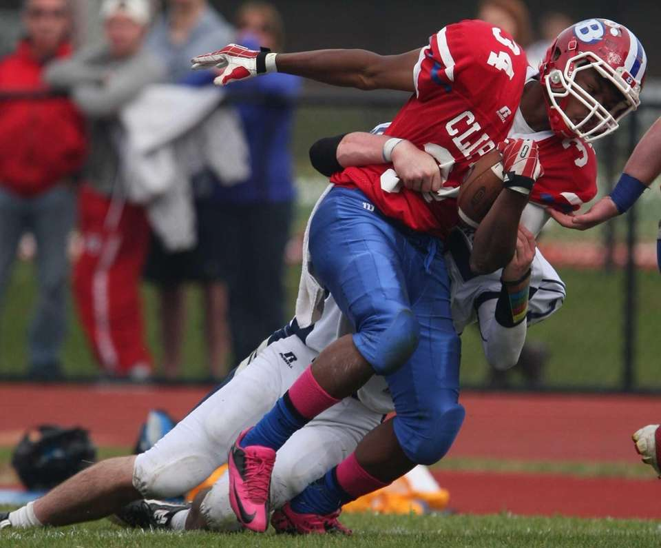 Bellport's Jabari M'Bhaso (front) gets brought down by