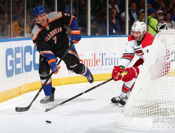 Matt Carkner of the Islanders looks to clear