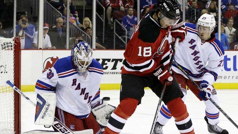 Rangers goalie Henrik Lundqvist, left, blocks a shot