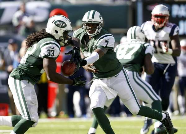 Geno Smith (no. 7) hands the ball off