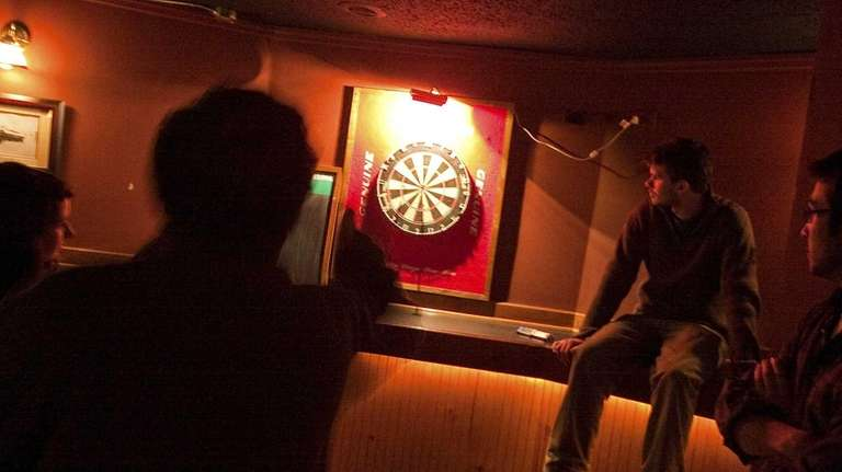 Group of patrons play a round of darts