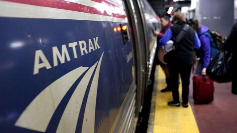 People board an Amtrak train at Penn Station