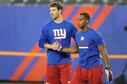 Eli Manning, left, and Victor Cruz interact before