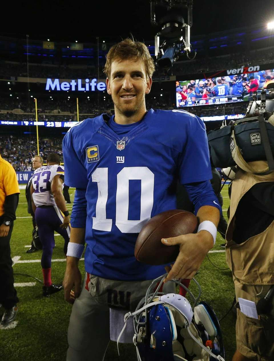 Eli Manning walks off the field after defeating