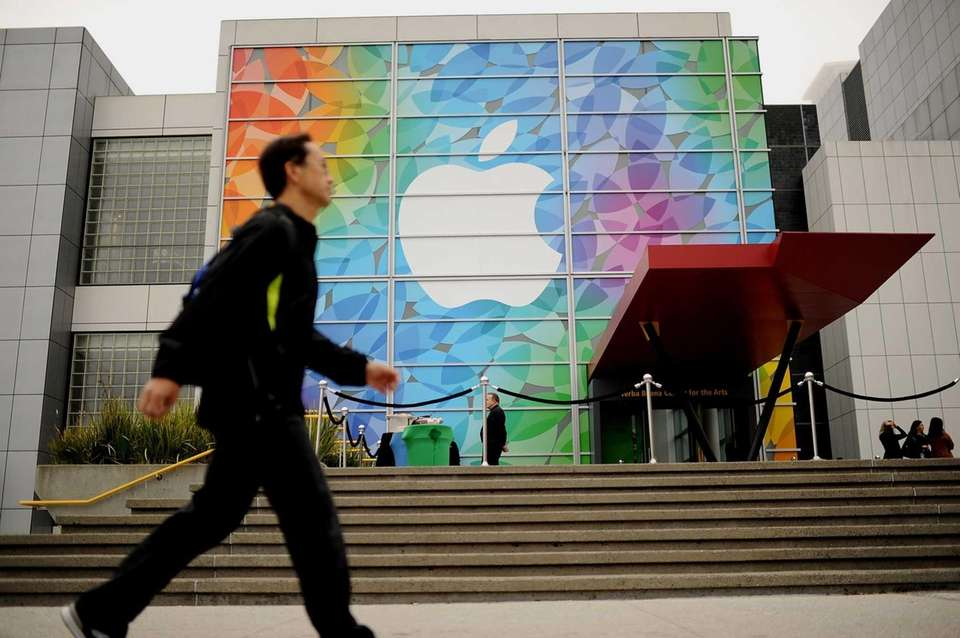 A pedestrian passes an Apple logo shortly before
