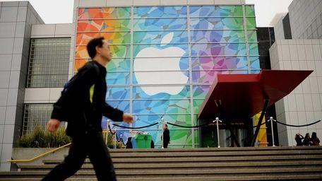 A pedestrian passes an Apple logo shortly before