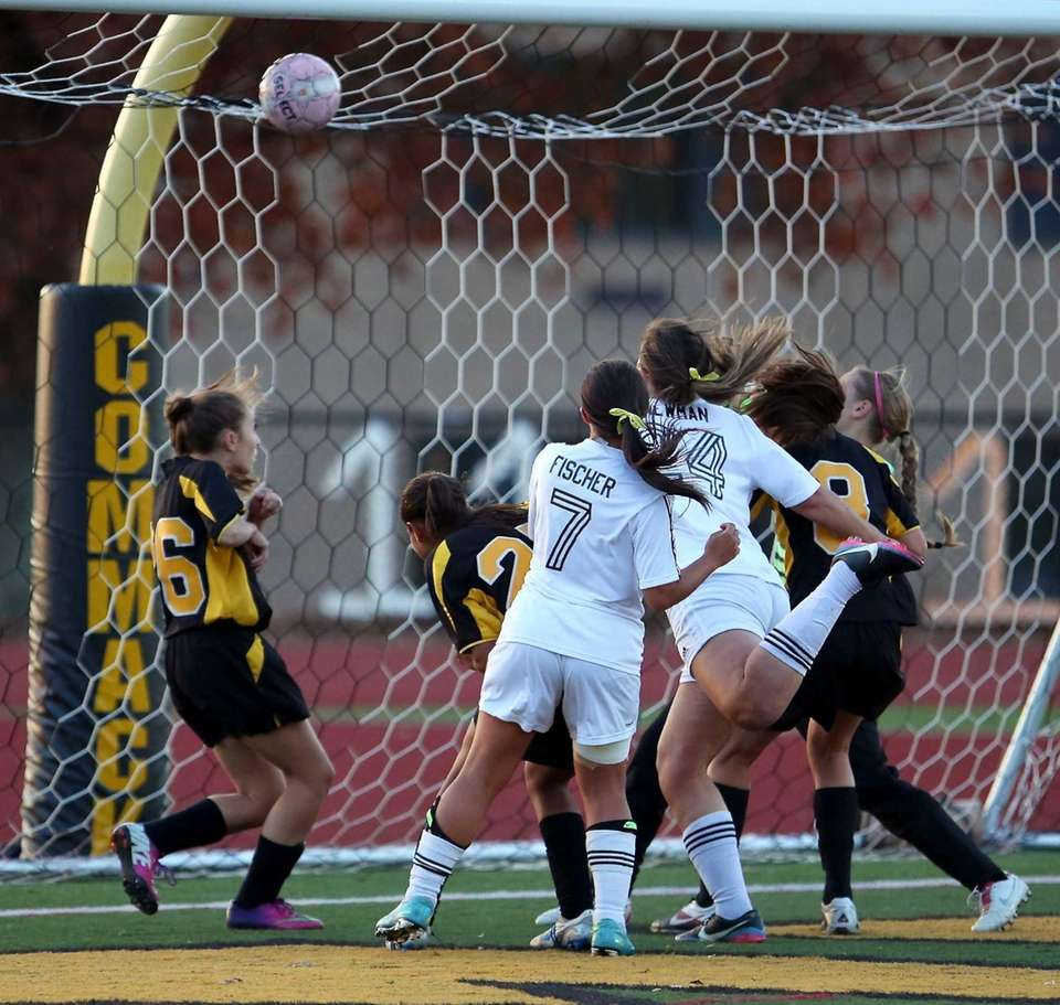 Commack's Jessica Newman, middle, heads the ball into