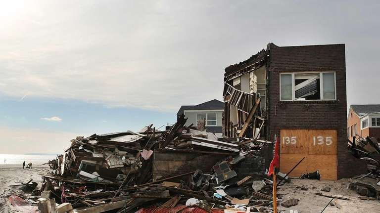 A destroyed home is viewed along the beach